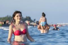 Girl in pink bathing suit standing waist-deep in sea water. Royalty Free Stock Image