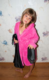 Girl in pink bathrobe. Choose black clothes to wear Royalty Free Stock Images