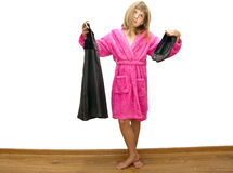 Girl in pink bathrobe. Choose black clothes to wear Stock Photo