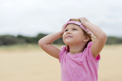 Girl in pink at the beach 2. Girl in pink shirt and hat at the beach Royalty Free Stock Image