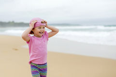 Girl in pink at the beach 3. Girl in pink shirt and hat at the beach Royalty Free Stock Images