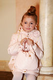 Girl in pink-beige coat with bag in her hands sits Royalty Free Stock Image