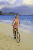 Girl in pink bikini riding her bike Royalty Free Stock Photo