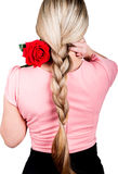 Girl in a pink blouse, her hair braided. on the shoulder of a red rose. back view. isolated on white background Royalty Free Stock Image