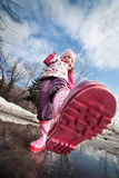 Girl in pink boots. A little girls pink boots splashing in a muddy puddle Royalty Free Stock Photography
