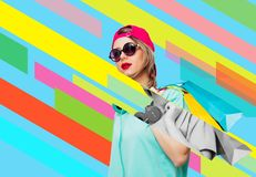 Girl in pink cap and blue t-shirt with shopping bags stock photo