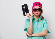 Girl in pink cap and blue t-shirt with VHS cassette. Beautiful young girl in pink cap and blue t-shirt with VHS cassette on white background stock image