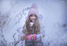 Beautiful girl in a pink cap with bumbony in a winter. royalty free stock images