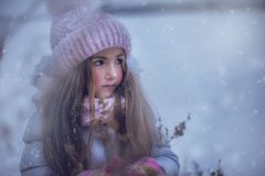 Beautiful girl in a pink cap with bumbony in winter. stock images
