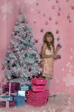 Girl in pink at the Christmas tree Royalty Free Stock Photography