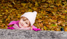 Girl in pink clothes on golden leaves background. Early autumn time - Girl in pink clothes on golden leaves background Royalty Free Stock Photo