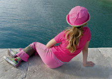 Girl with pink clothes and sea. Female in pink cap (clothes) and blue-green Adriatic sea (Croatia-Dalmatia Royalty Free Stock Image