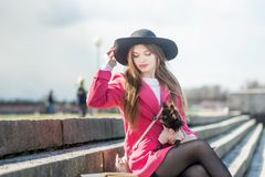 Girl in a pink coat and a black hat with a small dog stock photography
