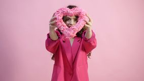 Girl in pink coat with heart in hand on pink background.Love Concept. Beautiful seductive young woman. Valentines Day. Gift. On pink background stock video