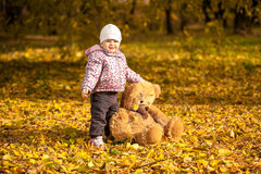 Girl in pink coat holding big teddy bear at park Royalty Free Stock Photo
