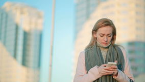 Girl in a pink coat with phone walks on a modern city. background of skyscrapers. Girl in a pink coat with phone walks on a modern city on the background of stock video