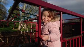 Girl in pink coat on a red climbing frame stock images