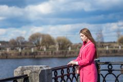 The girl in the pink coat is sad on the waterfront stock photos
