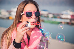 Girl in pink colors blowing soap bubbles Stock Image
