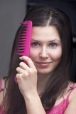 Girl with a pink comb Stock Photos