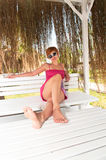 Girl in pink dress on bench Royalty Free Stock Photography