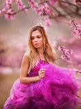 Girl in pink dress in blooming gardens. Beautiful angel in the flower garden royalty free stock image