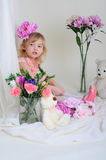 The girl in a pink dress with a flower on her head. Girl in a pink dress near the bouquets of flowers sitting on the floor Royalty Free Stock Image