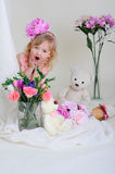 The girl in a pink dress with a flower on her head. Surprised girl in a pink dress near the bouquets of flowers sitting on the floor Royalty Free Stock Image