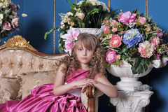 Girl in a pink dress among the flowers Stock Images