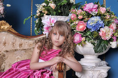 Girl in a pink dress among the flowers. Blond Flower girl wearing a pink dress Royalty Free Stock Photography