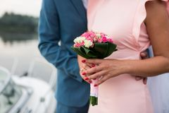 The girl in a pink dress and a guy in a suit are holding a beautiful bouquet of white and pink roses.. Wedding details. Wedding. The girl in a pink dress and a Stock Images