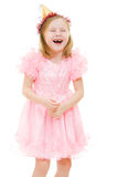 A girl in a pink dress and hat laughing Stock Photos
