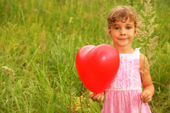 Girl in pink dress holding red balloon. Royalty Free Stock Photos