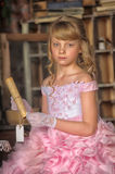 Girl in a pink dress holding a scroll Stock Image