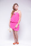 Girl in a pink dress holding a teddy bear and smiling Royalty Free Stock Photography