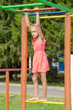 The girl in the pink dress on horizontal bar climbing on playground Royalty Free Stock Photos
