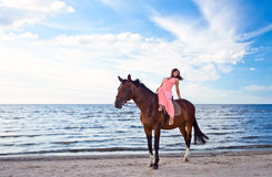 Girl in pink dress with horse on seacoast Stock Photography