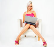 Girl in pink dress with laptop. Girl in pink dress sitting on white chair with laptop stock photos