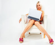 Girl in pink dress with laptop. Girl in pink dress sitting on white chair with laptop stock photo