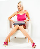 Girl in pink dress with laptop. Girl in pink dress sitting on white chair with laptop stock photography