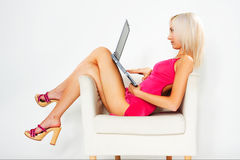 Girl in pink dress with laptop Royalty Free Stock Photography