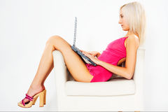 Girl in pink dress with laptop. Girl in pink dress sitting on white chair with laptop royalty free stock photo