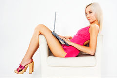 Girl in pink dress with laptop. Girl in pink dress sitting on white chair with laptop royalty free stock image