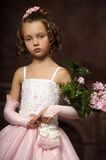 Girl in a pink dress with lilac in the hands Stock Images
