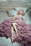 Girl in pink dress lying on a lush bed. Stock Photography
