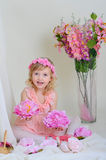 The girl in a pink dress. Girl in a pink dress near the bouquets of flowers sitting on the floor holding flowers Royalty Free Stock Image