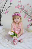 The girl in a pink dress. Girl in a pink dress near the bouquets of flowers sitting on the floor holding flowers Royalty Free Stock Photos