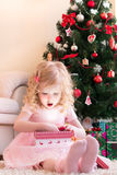 Girl in pink dress opening gift Royalty Free Stock Photos