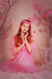 The girl in a pink dress and pink wreath. The girl in the studio in a pink dress and pink wreath on a background of flowering trees Stock Images