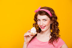 Girl in pink dress pinup-style eats cake with cream stock photo